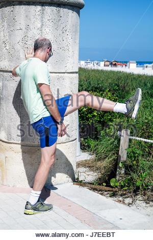 Miami Beach Florida Mann Läufer Jogger Dehnung Ausübung erhöhen Bein vor dem Ausführen der Aufwärmübung - Stockfoto