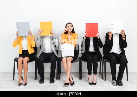 Bild einer glücklich denken Frau suchen Sie beiseite, während ihre Kollegen sitzen im Amt für Flächen mit Ordnern. - Stockfoto