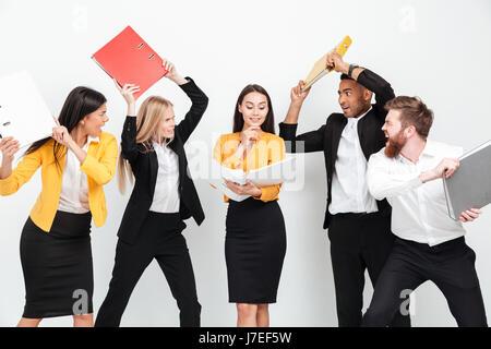Bild von glücklichen Frau hält Ordner während eine Gruppe von wütenden Kollegen kämpfen isoliert im Amt. - Stockfoto