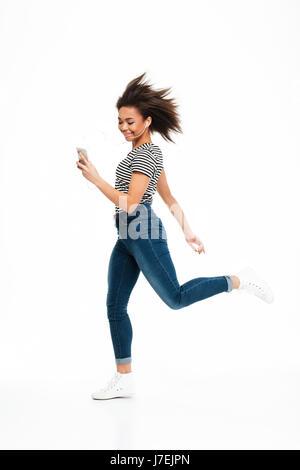 In voller Länge Portrait von ein fröhliches unbeschwertes afrikanische Mädchen springen beim Musikhören über Kopfhörer - Stockfoto