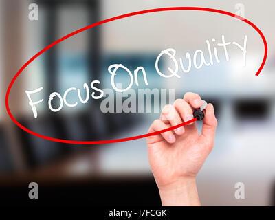 Hand des Mannes Fokus auf Qualität mit schwarzem Filzstift auf Bildschirm zu schreiben. Auf Hintergrund isoliert. - Stockfoto