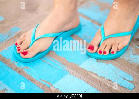 Lady die Füße mit rotem Nagellack in Sandalen auf dem sandigen Strand am Meer im Sommer auf Holzsteg. - Stockfoto