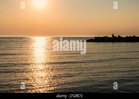 Sonnenuntergang über dem Meer bei Ahrenshoop Mann Angeln im Meer aus Felsen, Mecklenburg-Vorpommern, Deutschland - Stockfoto
