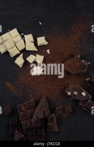 Auswahl an verschiedenen Arten von Schokoriegeln stürzte in Stücke über hölzerne Hintergrund - Stockfoto