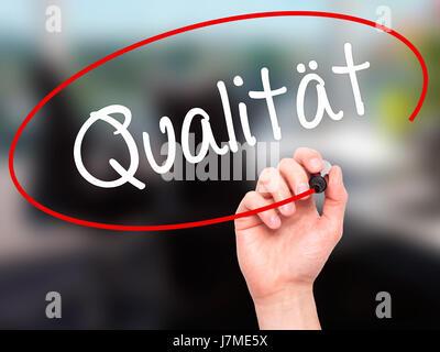 Hand des Mannes Schreibqualität (Qualitat in deutscher Sprache) mit schwarzen Balken am Bildschirm. Auf Hintergrund - Stockfoto