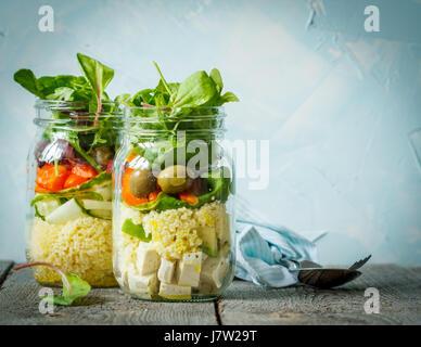 Bunter Salat mit Couscous, Tofu und Gemüse im Glas. Liebe für eine gesunde vegane Ernährung Konzept - Stockfoto