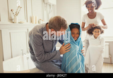 Multi-ethnischen Eltern Trocknung Töchter mit Handtüchern nach Badezeit im Badezimmer - Stockfoto