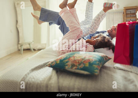 Vater und Töchter im Pyjama treten Beine auf Bett - Stockfoto
