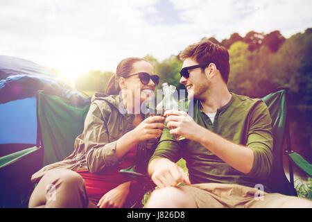 glückliches Paar klirrende Getränke an Camping Zelt - Stockfoto