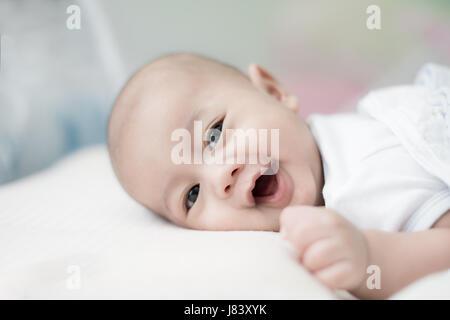 Porträt von niedlichen 3 Monate asiatisches Baby junge liegend auf einer Decke und Lächeln. - Stockfoto