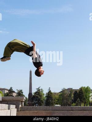 Junger Mann tut einen Back Flip im Hintergrund Obelisk. Parkour im urbanen Raum. Sport in der Stadt. Sportliche - Stockfoto