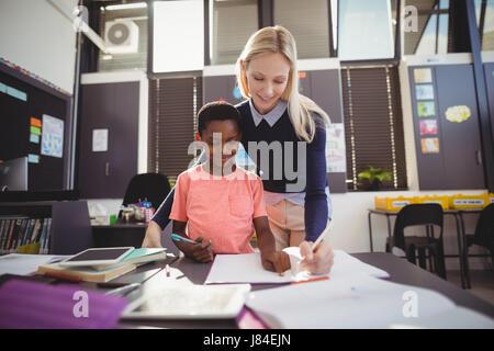 Lehrer Schulmädchen bei ihren Hausaufgaben im Klassenzimmer in der Schule helfen