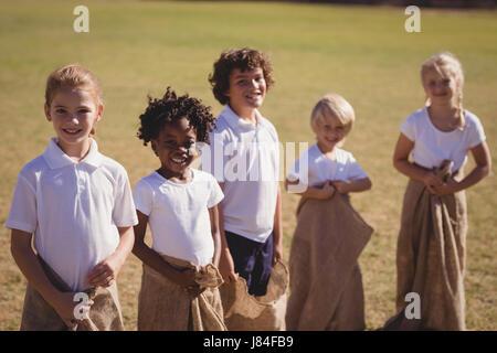 Porträt von glücklichen SchülerInnen stehen im Sack während Rennen an einem sonnigen Tag Stockfoto