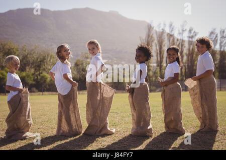 SchülerInnen, die Spaß beim Sackhüpfen im Park an einem sonnigen Tag Stockfoto