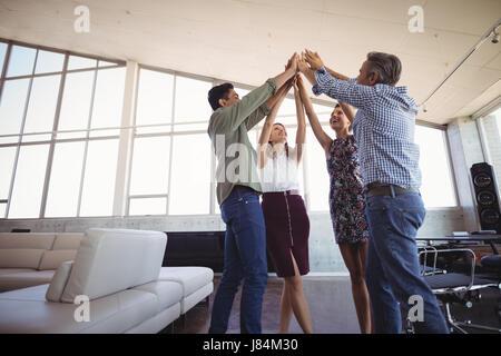 Geschäftsleute, die Hände zusammen am Kreativbüro erhebend - Stockfoto