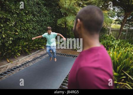 Seitenansicht von Vater auf Sohn springen auf dem Trampolin - Stockfoto