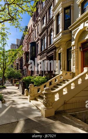 Reihe von Brownstones mit Schwellen und Ornament im Morgenlicht. Upper West Side Street, Manhattan, New York City - Stockfoto