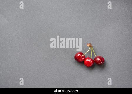 Kirschen auf grauem Hintergrund. Ansicht von oben - Stockfoto