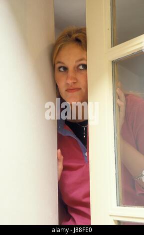 junge Frau, die verdächtig aus Fenster Stockfoto