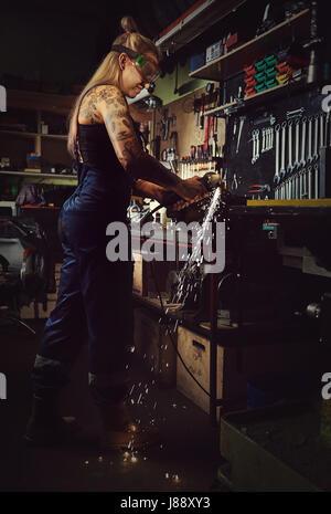 Frau Mechaniker arbeiten in einer Motorradwerkstatt