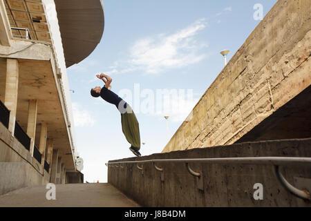 Junger Mann einen Back Flip zu tun. Parkour im urbanen Raum. Sport in der Stadt. Sportliche Aktivität. - Stockfoto