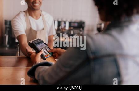 Schuss von Kunden, die Eingabe der Pin-Nummer in Maschine am Schalter im Café beschnitten. Konzentrieren Sie sich - Stockfoto