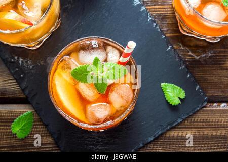 Pfirsich Eistee. Eistee mit Pfirsich Scheiben, Minze und Eiswürfel auf Schiefer und Holz rustikal Hintergrund hautnah. - Stockfoto