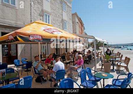 Menschen mit Mittagessen auf einer Terrasse im Hafen von Rab Kroatien - Stockfoto