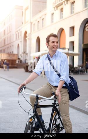 Mann reitet auf seinem Fahrrad in der Stadt - Stockfoto