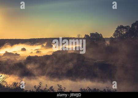 Goldene Stunde am Ufer des Flusses mit Nebel über Bäume und Wasser in blau und orange Farben bei Sonnenaufgang - Stockfoto