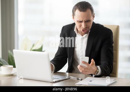 Geschäftsmann wütend, weil zum falschen Zeitpunkt oder lästigen Anruf in seine Arbeiten am Laptop im Büro mal. Unternehmer - Stockfoto