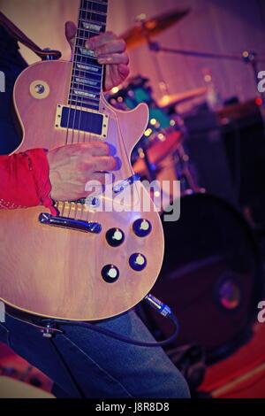 Gitarrist spielt e-Gitarre auf der Bühne während eines Konzerts - Stockfoto