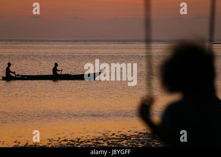 Mädchen Schaukeln am Meer, während ein Fischer Boot vorbeifahren - Stockfoto