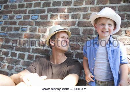 Vater und Sohn Wand gelehnt und kauen Grass - Stockfoto
