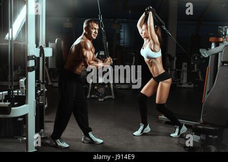 Mann und Frau trainiert Muskeln im Fitness-Studio.  Sie trainieren mit Maschinen für Bodybuilder. - Stockfoto