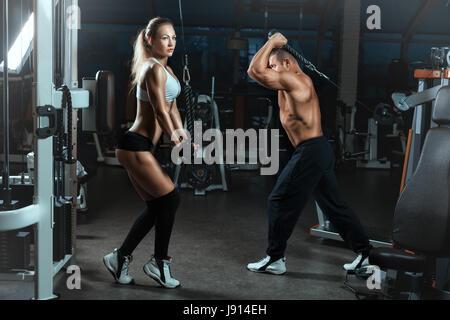 Mädchen und der Mann hinein für Sport in der Halle mit Maschinen für Bodybuilder. Sie Heben schwerer Gewichte, um - Stockfoto