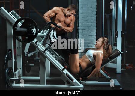 Bodybuilder Züge Mann der eine Frau. Frau auf die Maschine, Ihre Beinmuskeln zu schwingen. - Stockfoto