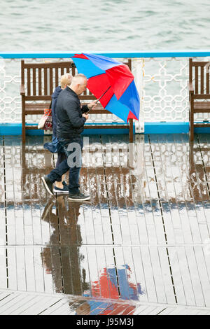 Ein paar Auseinandersetzung mit ihren bunten Regenschirm zum Schutz vor der nassen und windigen Wetter auf dem Holzsteg - Stockfoto