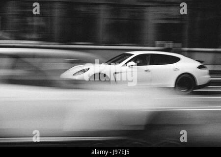 Verschwommene Auto beschleunigt auf der Straße der Stadt. Schwarz / weiß Filmverarbeitung. Abstrakte Speed-Hintergrund - Stockfoto