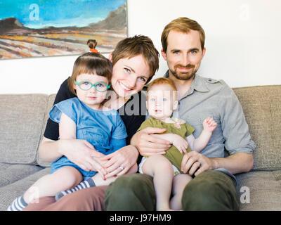 Porträt von Eltern mit Töchtern (12-17 Monate, 2-3) auf Sofa - Stockfoto