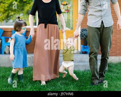Eltern mit Töchtern (2-3, 12-17 Monate) stehen auf dem Rasen - Stockfoto