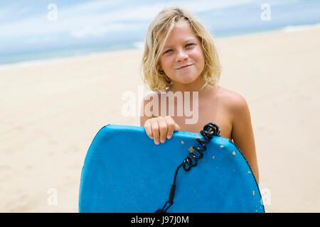 Jungen (8-9) stehen am Strand und hält Surfbrett - Stockfoto