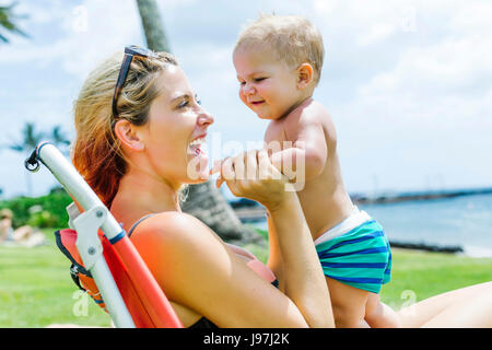 Frau sitzt unter Palme mit kleinen Sohn (18-23 Monate) - Stockfoto