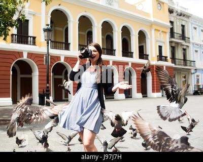 Puerto Rico, San Juan, Frau auf dem Platz unter Tauben - Stockfoto
