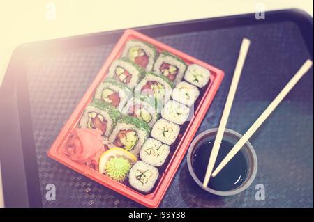 Japanisches Sushi in roten Kunststoff-Behälter für den Transport von Lebensmitteln auf schwarz. Roll hergestellt - Stockfoto