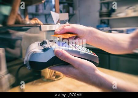 Nahaufnahme einer Hand mit einer kontaktlosen Kreditkarte terminal bezahlen - Stockfoto