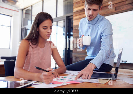 Mann auf eine Frau Schreibtisch beschreibt die Arbeit mit ihr - Stockfoto
