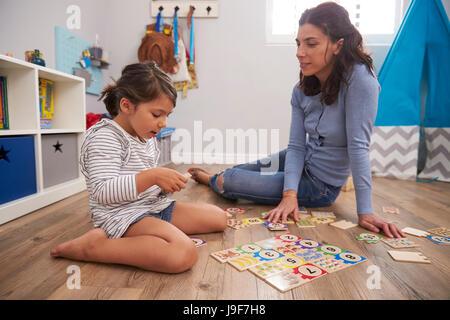 Mutter spielen Zahl Puzzlespiel mit Tochter im Spielzimmer - Stockfoto
