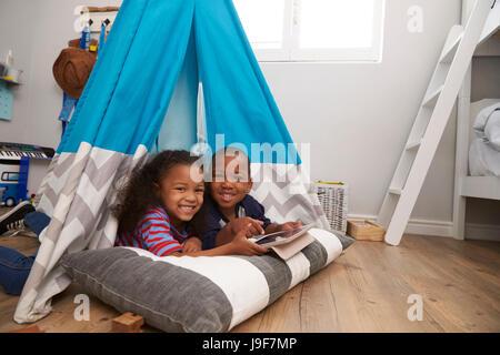Zwei Kinder im Zelt im Spielzimmer mit Digital-Tablette liegen - Stockfoto