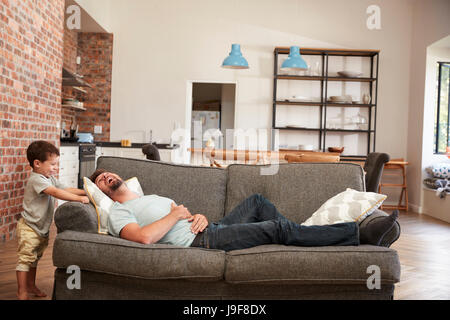 Vater und Sohn Spaß auf Sofa zusammen spielen - Stockfoto
